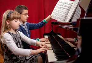 boy and a girl learn to play piano